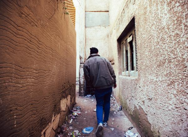 Alexandria, Egypt  A young man walks through the buildings of Agami, Alexandria, Egypt heading to the beach.  Agami is a city in the Alexandria Governorate of Egypt. Twenty kilometres west of Alexandria, the town is a popular destination for both local Alexandrians and tourists in Giza and Cairo.