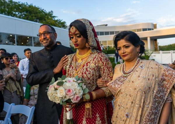 New Jersey, USA  Rafa Khundakar and her parents walk down the aisle on her wedding day during her traditional Bengali ceremony.