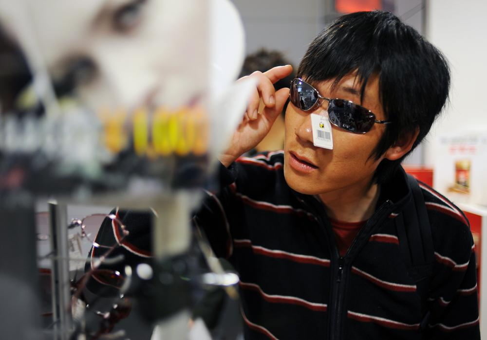 Li Chuan-hua checks and buys sunglasses as his own souvenir before boarding at duty free shop in Chubu Centrair International Airport, Nagoya, Japan. This is Li Chuan-hua's first time going back home since he left China three years ago.