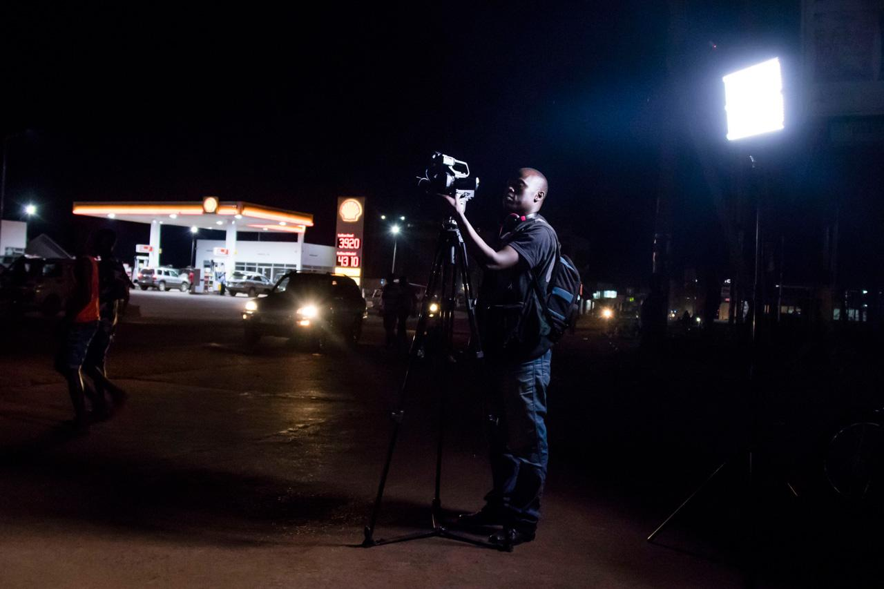 """NBS cameraman George Wesswa records a live link on a street in Gulu, Northern Uganda, at 8pm in preparation for a segment on social relations in the city, to be aired on the """"Live At 9"""" bulletin."""