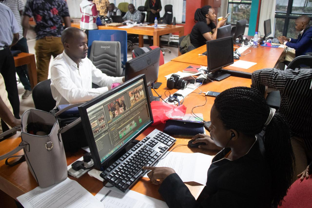 In the newsroom a video editor applies post production to video footage which will be aired on the Amasengejje bulletin.