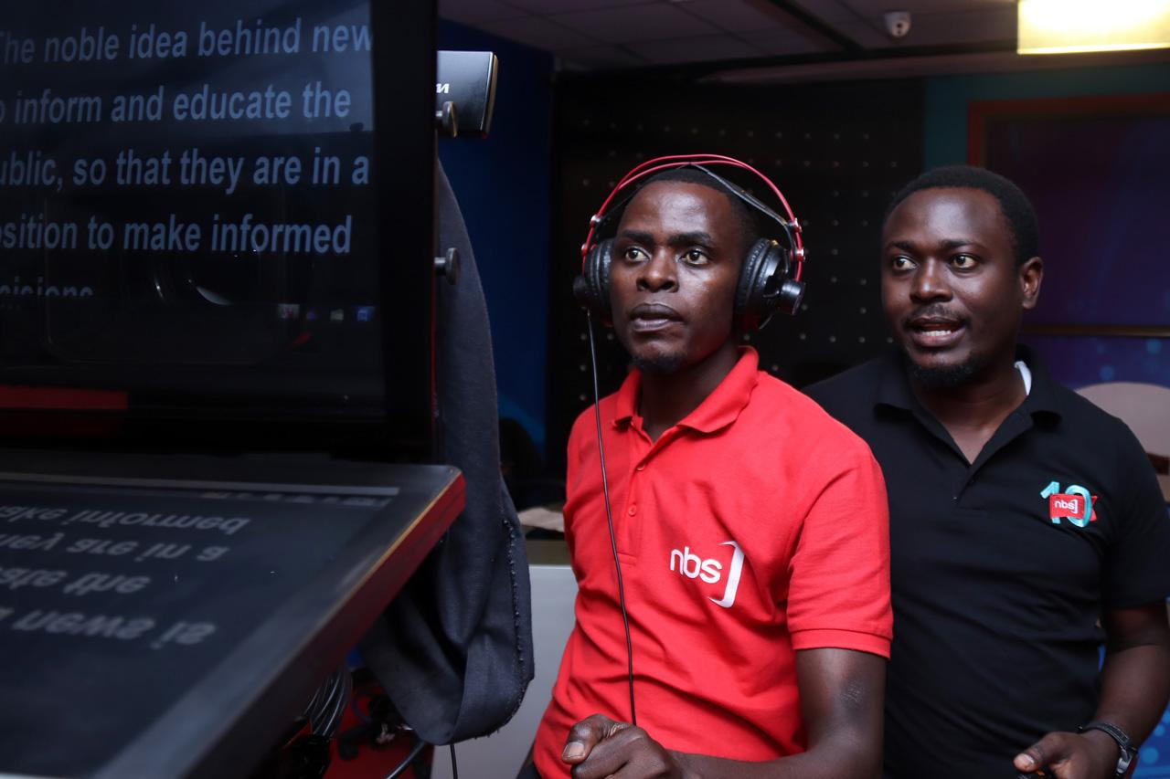 Studio cameraman Agrey Waguma (red shirt) and his director watch the live view from a camera as they discuss what positioning they will use during taping.