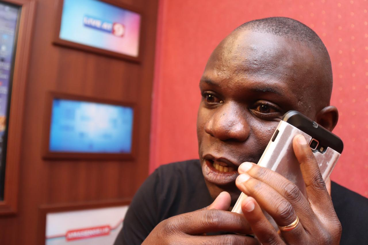"""Sports presenter and reporter Michael Kigozi takes a rushed phone call while on set for his """"Lunch Time Show"""" program."""