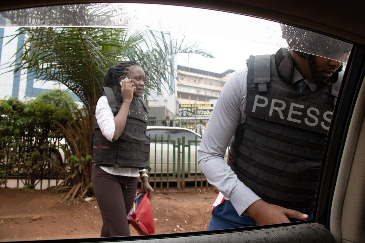 A light drizzle falls as reporters Violet Namata and Canary Mugume prepare to cover a protest against a new social media tax in Nakasero, central Kampala.