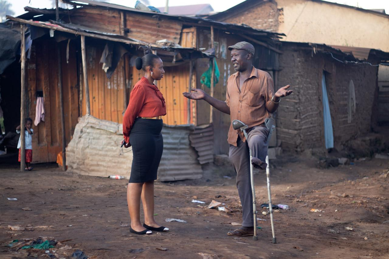 News reporter Victoria Bagaya listens during a conversation with a retired soldier in Kikaramoja zone, Kampala, as he explains to her about his life in the army and how he lost his left leg.
