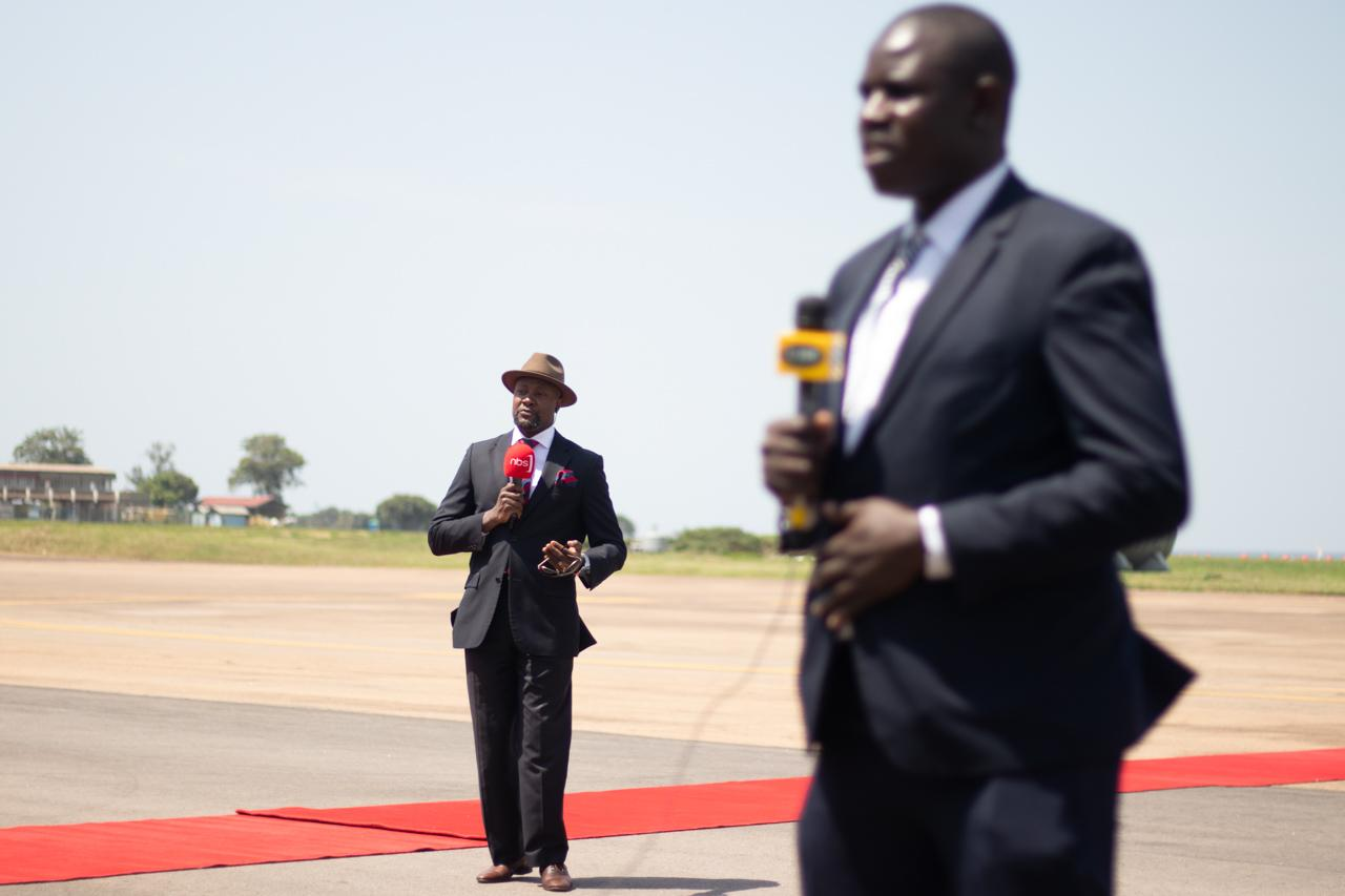 Senior reporter and anchor Samson Kasumba and another news reporter stand on the tarmac at Entebbe airport, recording updates on the arrival of the Indian Prime Minister to Uganda.