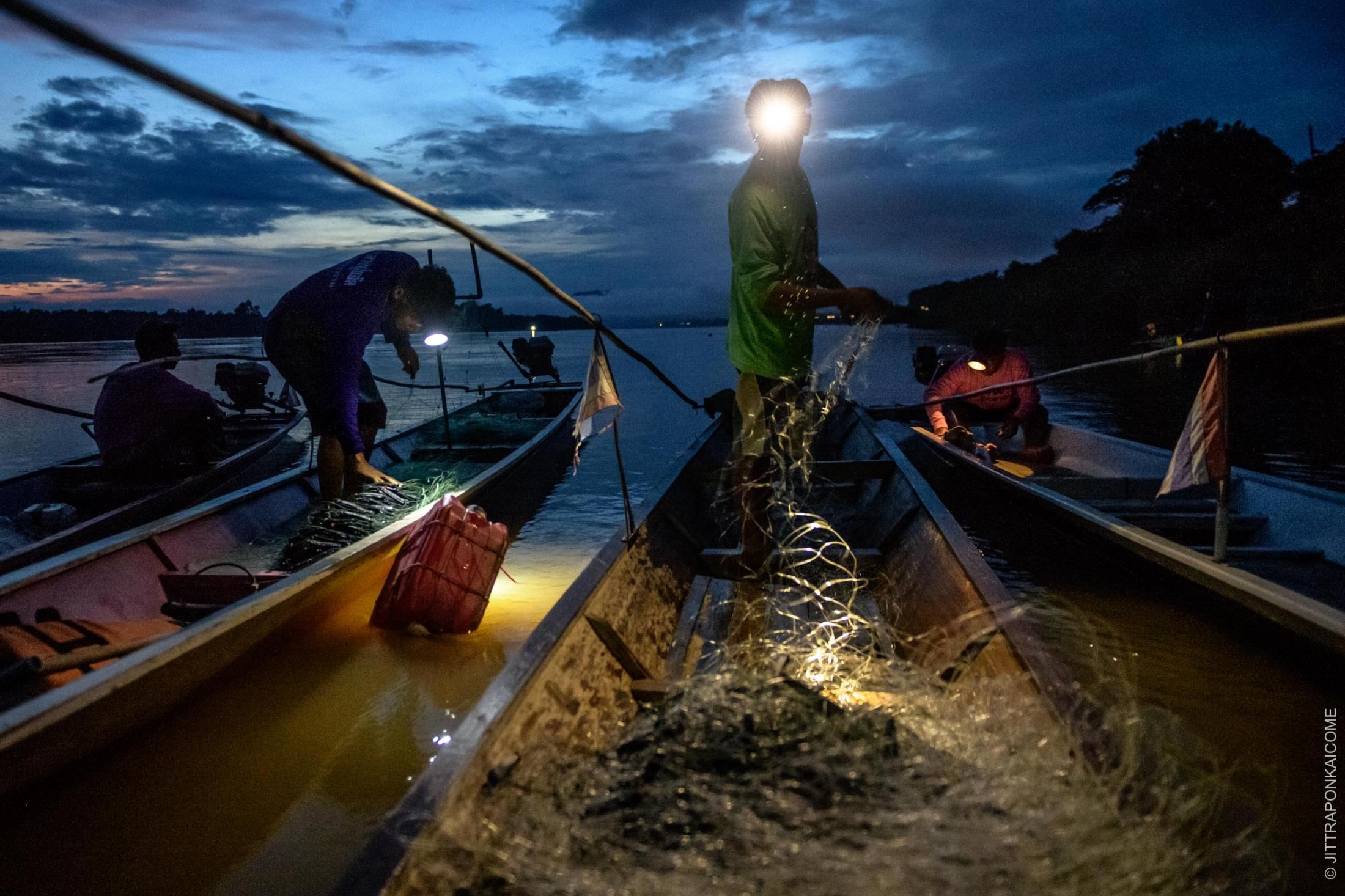 Fishers are preparing their nets in the small harbor, to catch fish at dawn amid fewer fish affected by unusual tidal resulted by Dams upper stream. In Loei, Thailand – August 2020.