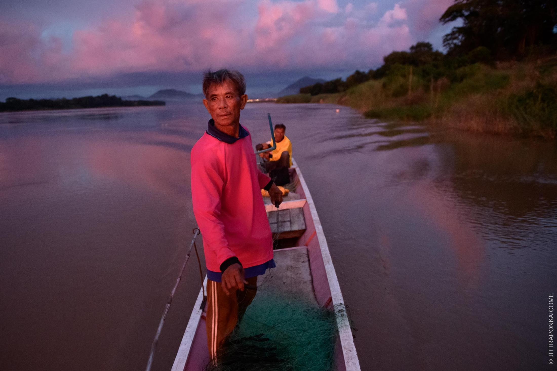 Prayoon Sanair is sailing out to find fish during the sunset. He is 63 years old and has been a fisherman in Chiang Khan since childhood. After the riverine ecosystem was negatively affected, due to the Xayaburi Dam and other dams upstream, making money from fishing became hard. He's now relying on alternative jobs such as farming rubber and work in the construction sector. In Loei, Thailand – August 2020.