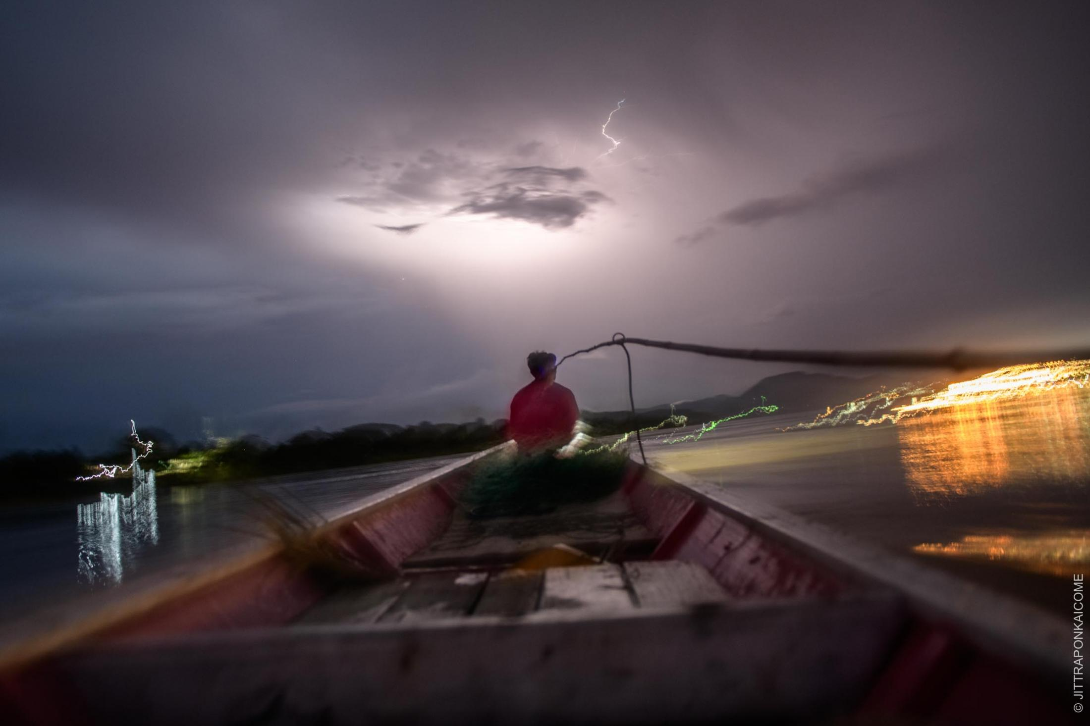 Unusual tidal activity combined with the lower water level of the Mekong River is affecting the ecosystem and livelihoods of thousands of people along the river banks. The future for fishers on the Mekong River is uncertain. The fisherman is sailing towards the rain storm. In Loei, Thailand – August 2020.