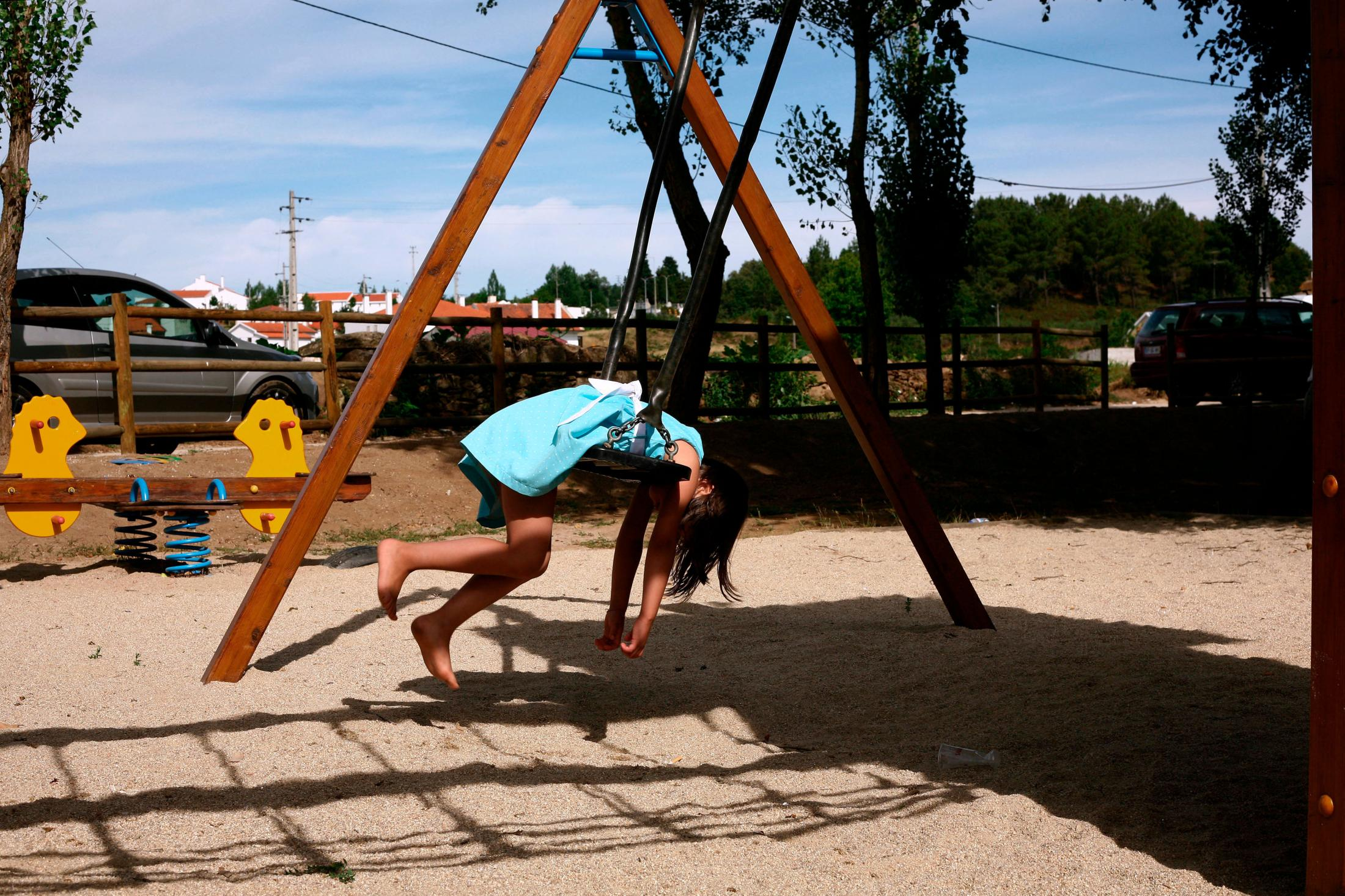 A girl plays on a swing at the river beach of Sabugal.