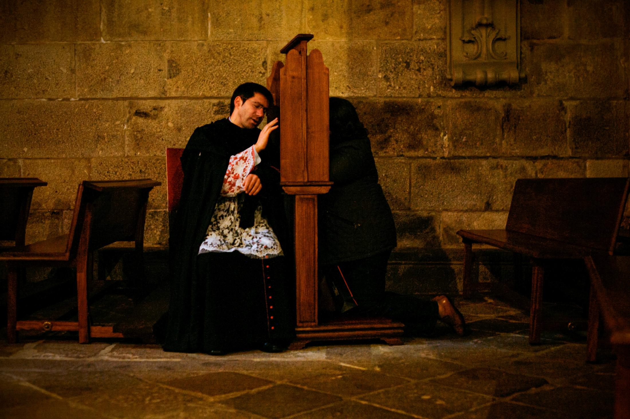 A priest makes a confession inside Braga cathedral.
