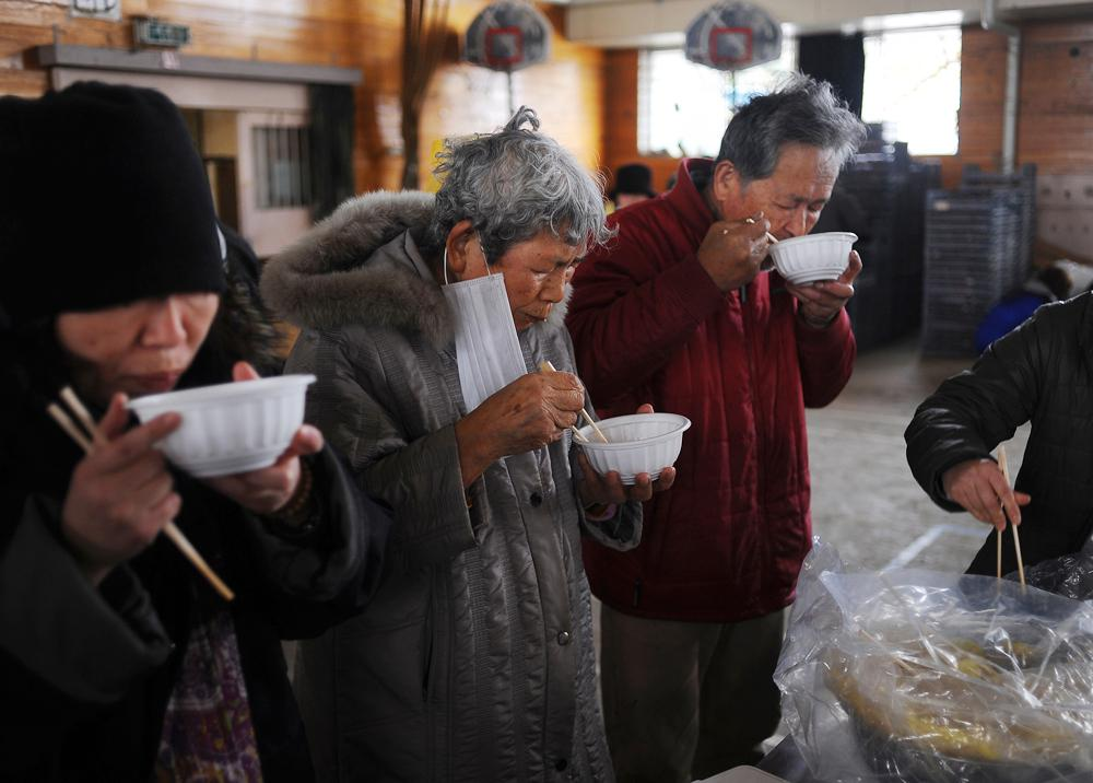 Tomi Hoshi (82),left and Seiji Hoshi (76),right  take emergency rations at the nearby evacuation center. It is the first time for them to venture out and have a hot meal because Tomi Hoshi has a heart condition and they stay in a room on the second floor of their home together.