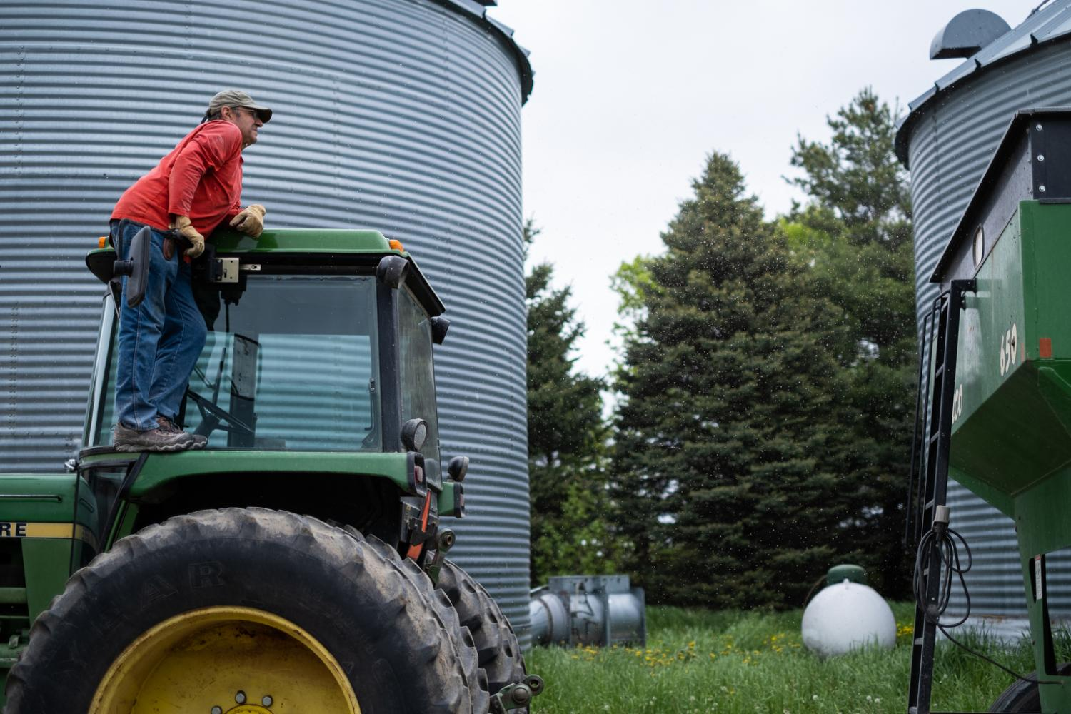 My dad watching to see how full the wagon is; he will then take the wagon of corn to town to sell.