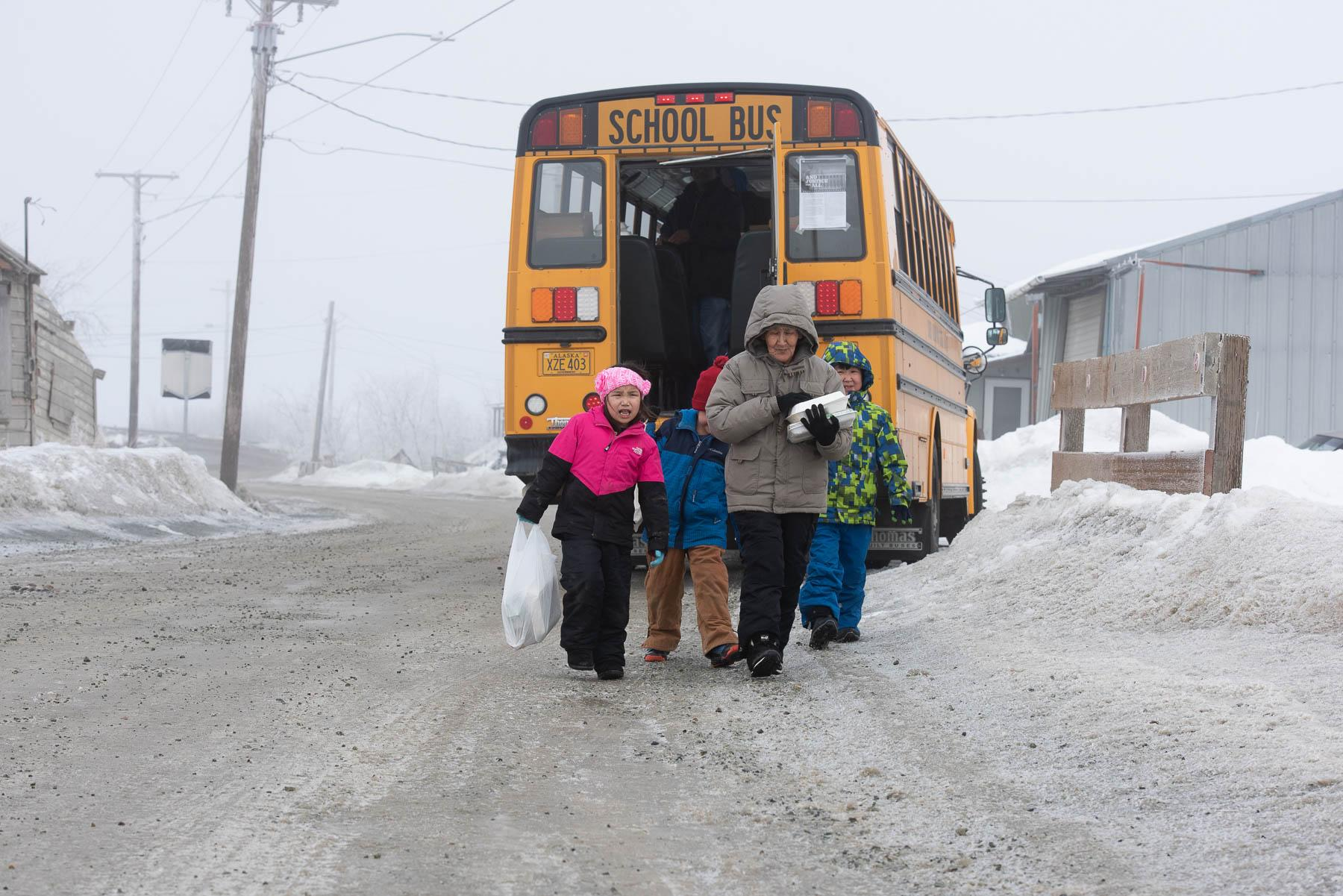 School children and their guardians picked up meals from bus stops around town on March 23, 2020. Schools across Alaska are closed following a state mandate put in place to slow the spread of COVID-19.