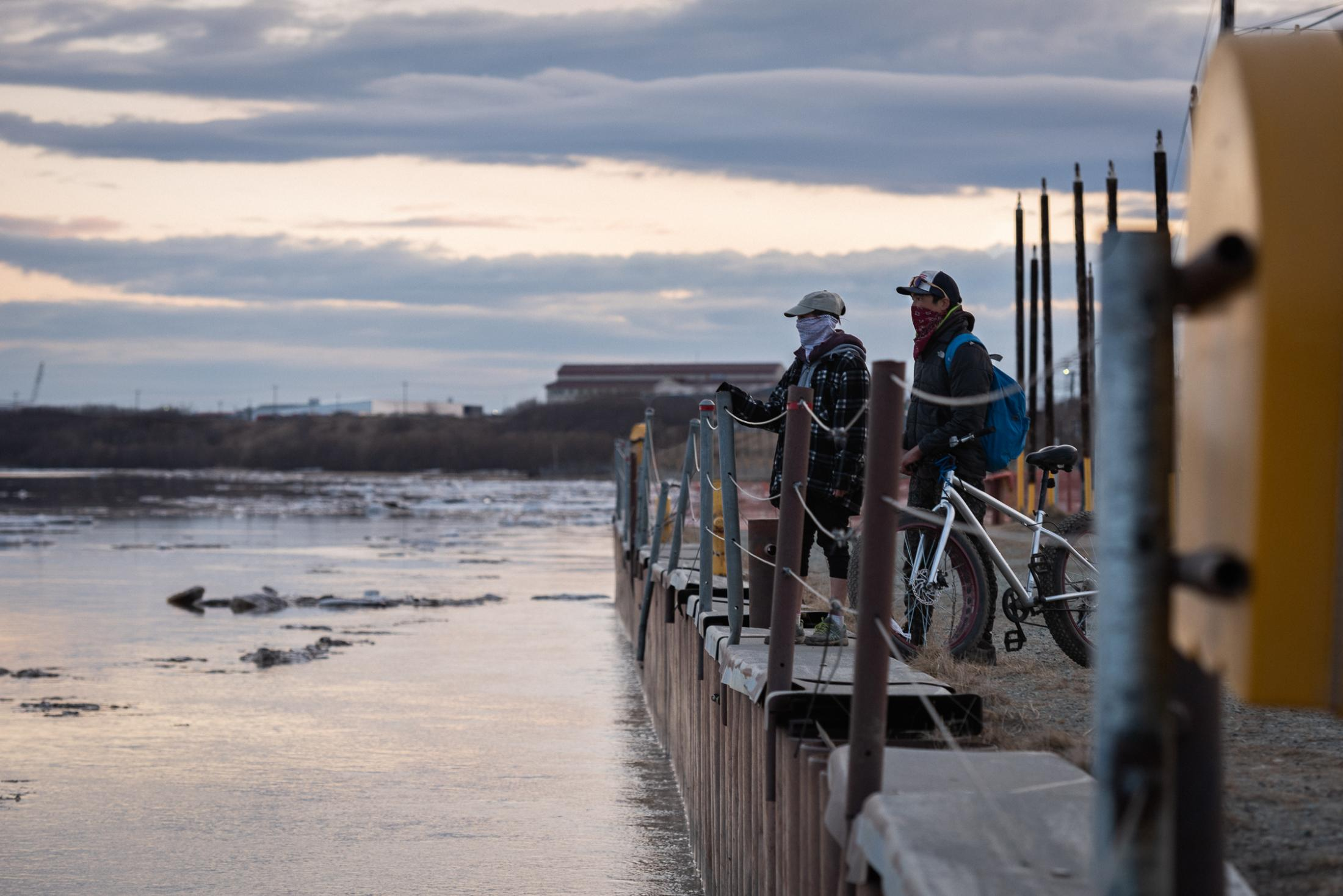 People watch the ice flow downriver during the Kuskokwim River break-up on May 4, 2020.