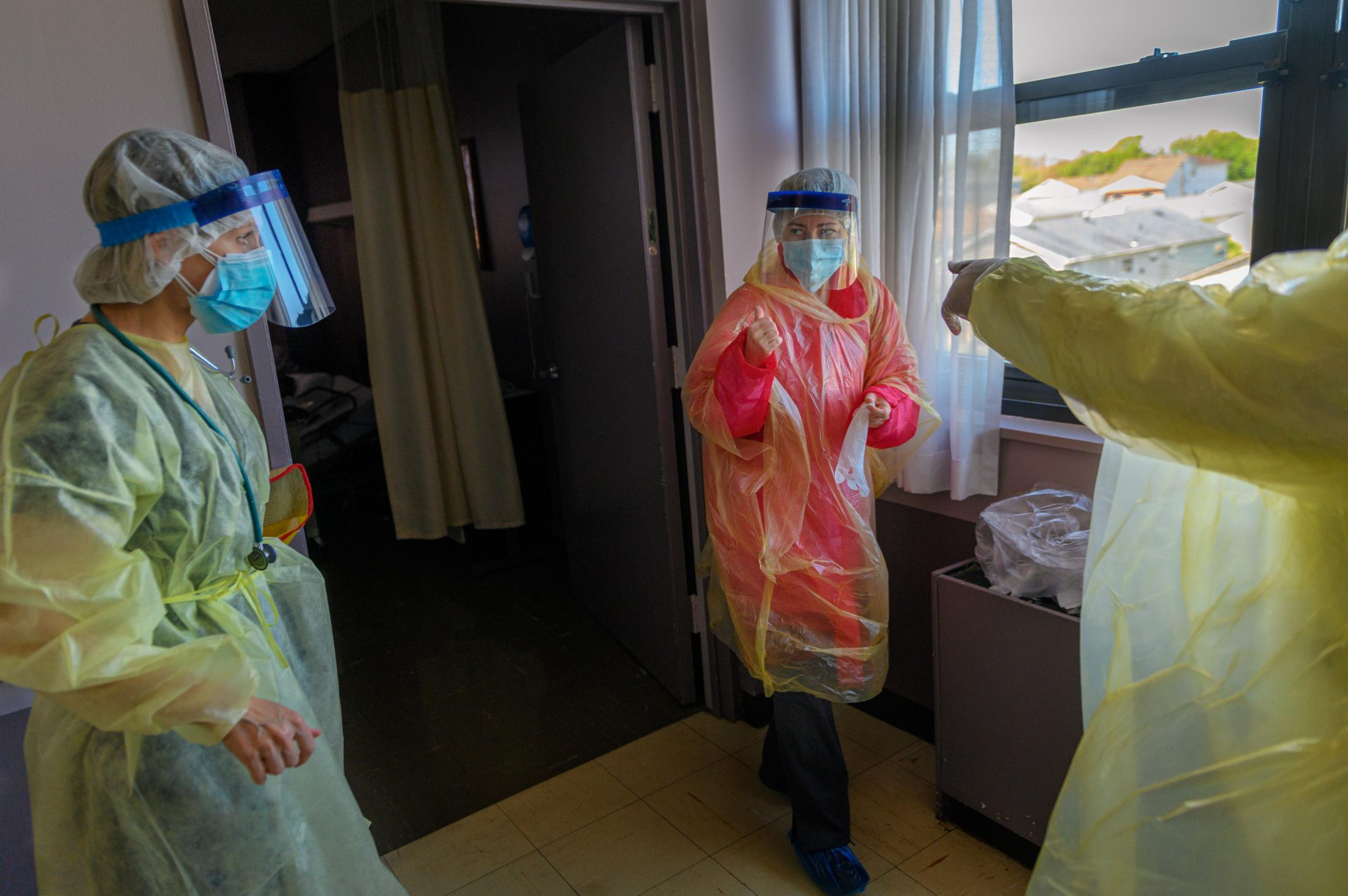 Jeanna and Lana put on extra level of PPE before entering a new patient's room for an evaluation session. The PPE protocol has been a work in progress as the facility has to improvise in order to protect their staff.