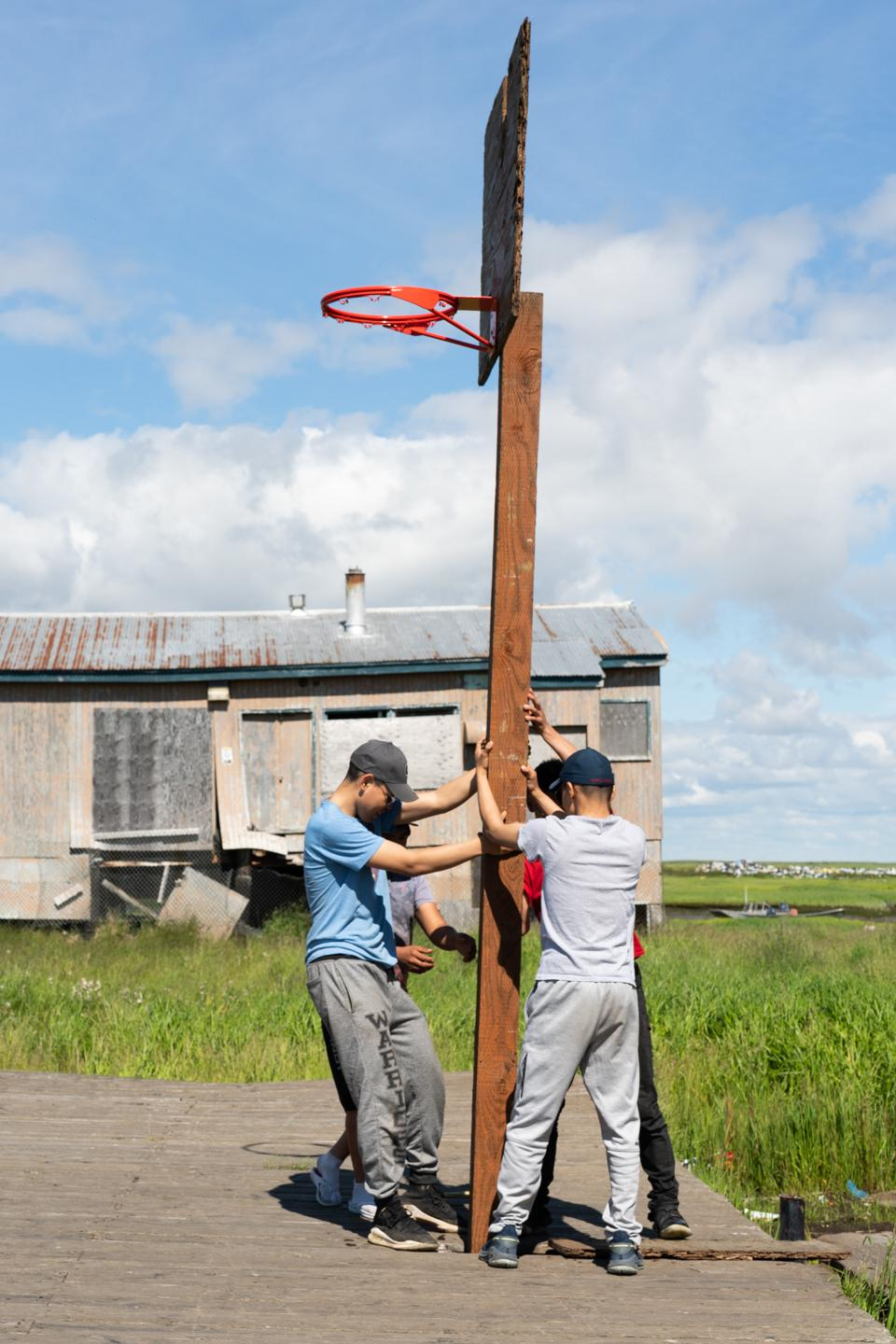 Youth fix their basketball court in Newtok, Alaska on July 12, 2020.
