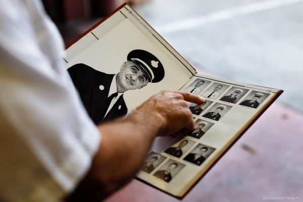 Firefighter Chief Frank Cercos IV indicates a photograph of his father in the SFFD Yearbook from 1997 at Fire Station No. 38 on Thursday, Nov. 14, 2019, in San Francisco, Calif. The photograph placed on the left side of the book is a portrait of his grandfather.