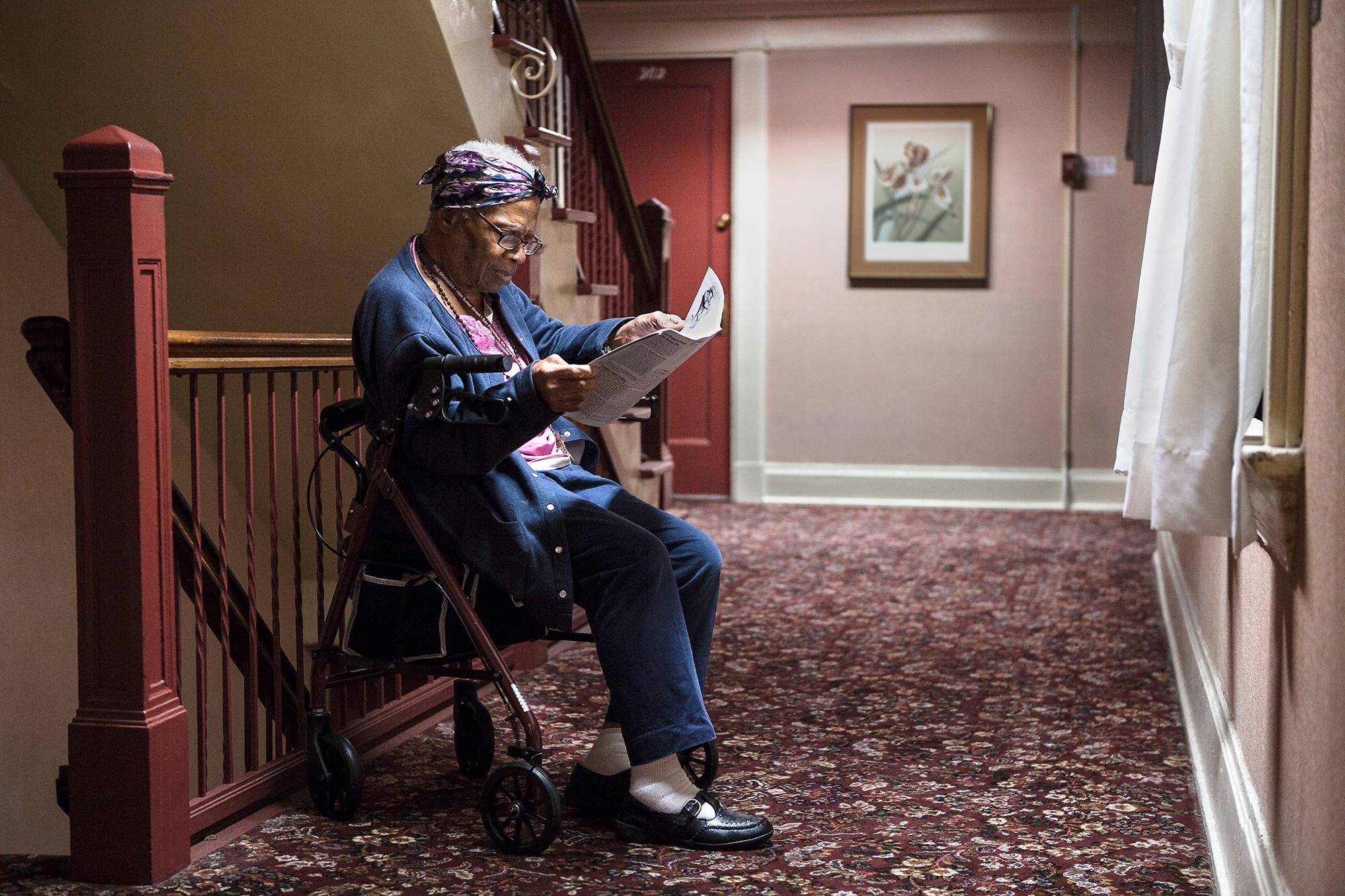 Carrie Doyle reads the newspaper sitting on her walking frame in a hallway at The Granada Hotel on Thursday, October 15, 2015, in San Francisco, California.