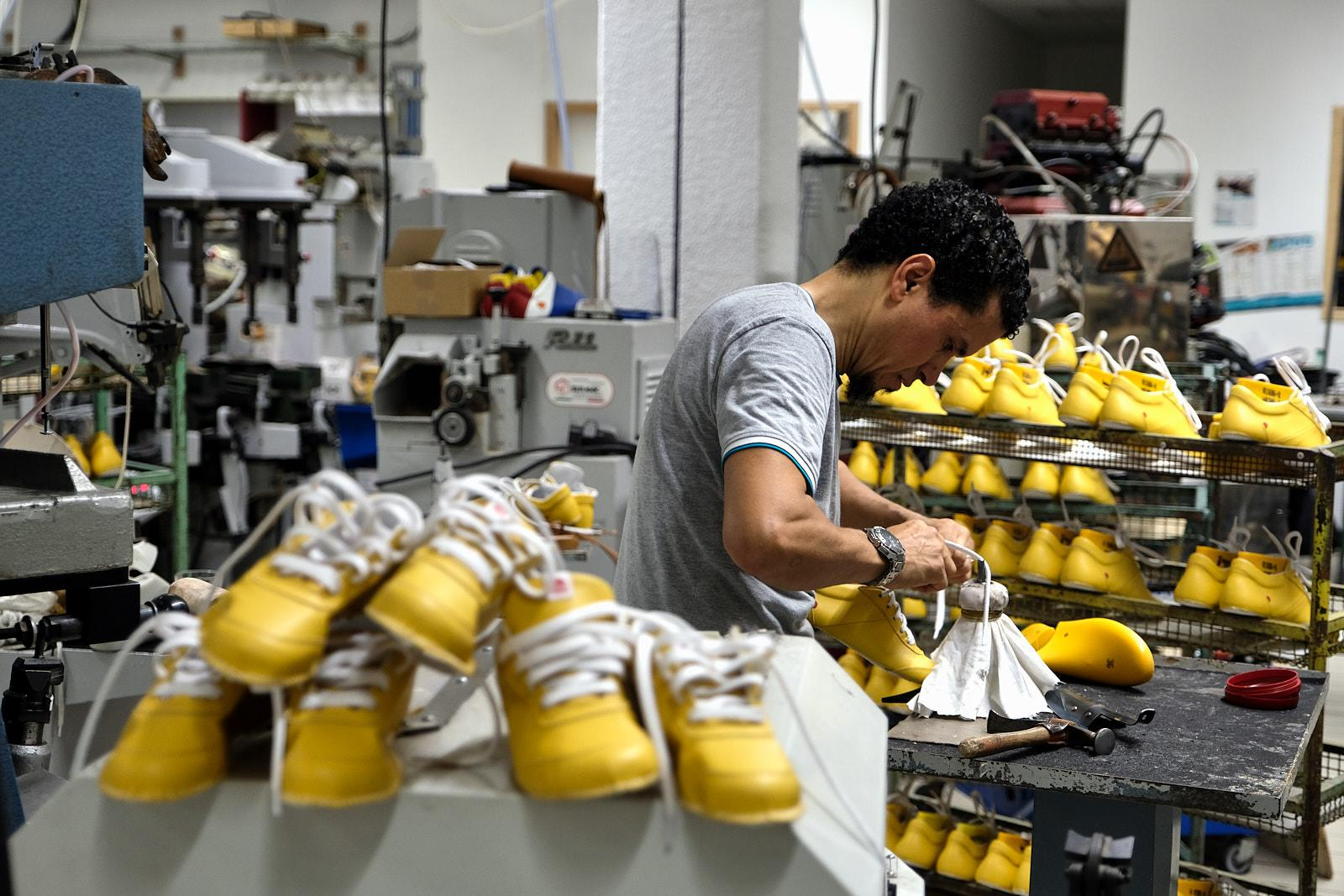 Mohammed fits size moulds on pairs of shoes.