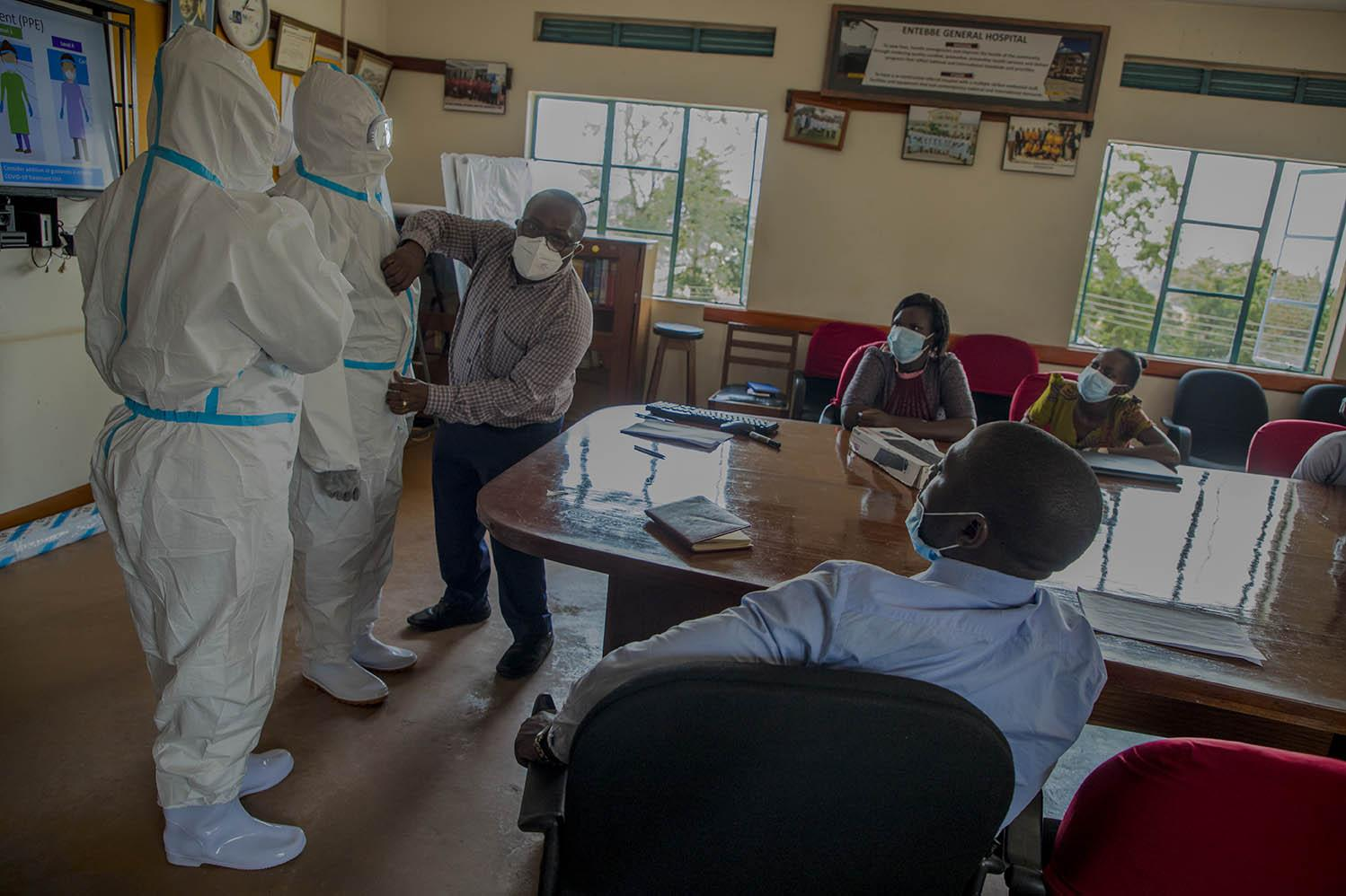 Volunteer medical workers at Entebbe General Hospital receiving training on how to use Personal Protective Equipment (PPE) while managing COVID-19 patients. Due to fear of catching the disease, many workers at the hospital withdrew from operating during this period  and the management embarked on training volunteers to have more staff support.