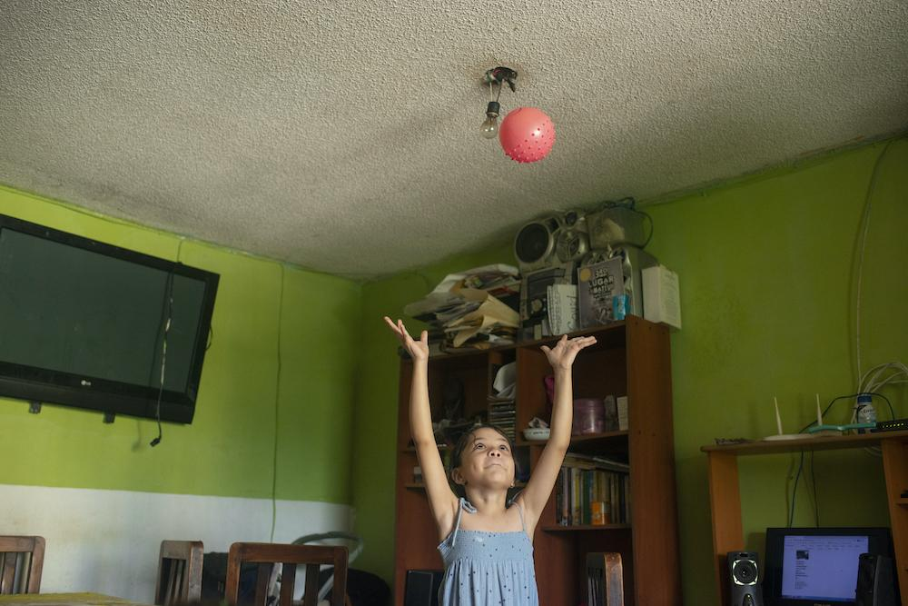 GUARENAS, VENEZUELA - JULY 12, 2020 Julieth's oldest step-daughter, Fabiola, plays with a ball in their home in Guarenas. The three bedroom apartment is shared among seven adults and eight young children. During lockdown, the family - all nurses - have had to coordinate schedules and days-long shifts to ensure someone was home, caring for their kids. CREDIT: Lexi Parra