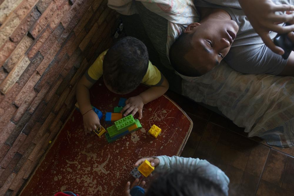 GUARENAS, VENEZUELA - JULY 12, 2020 Julieth's teenage nephew is on his phone while his cousins play with LEGOS in the living room on a Sunday. The children often go stir crazy from being inside so often, but they find entertainment in playing together. CREDIT: Lexi Parra