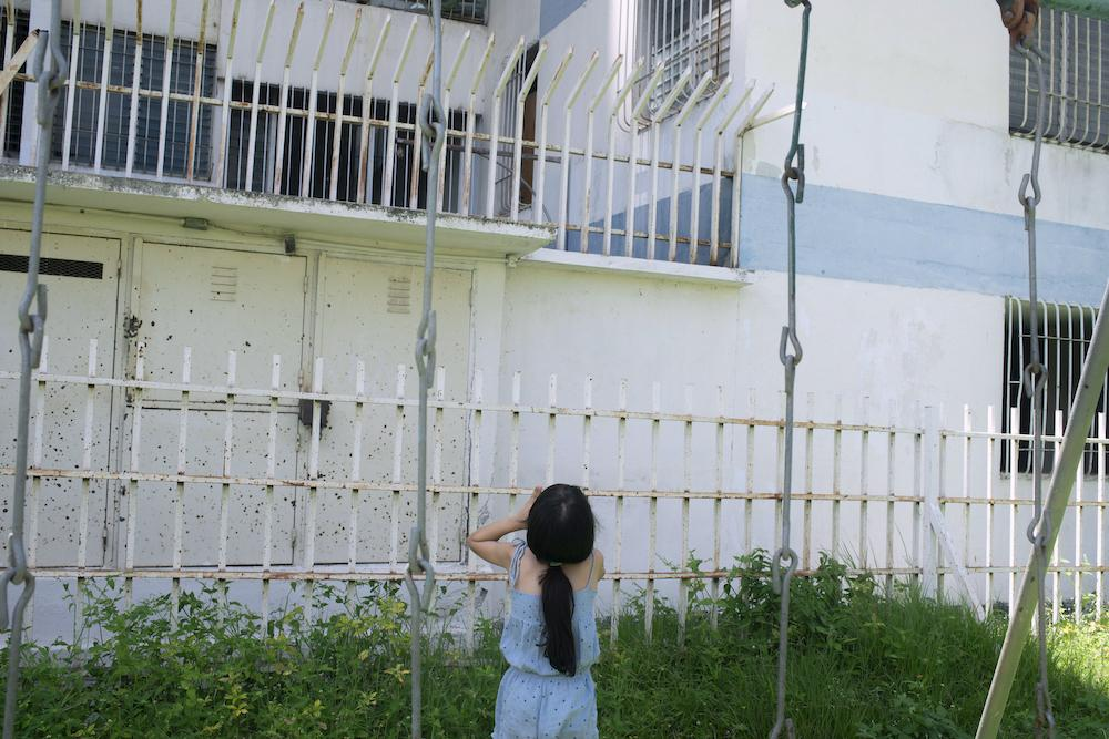 GUARENAS, VENEZUELA - JULY 12, 2020 Fabiola yells up to her cousin to come down and play in the park. Julieth is grateful they are able to get outside every once in a while, considering the restrictions. CREDIT: Lexi Parra