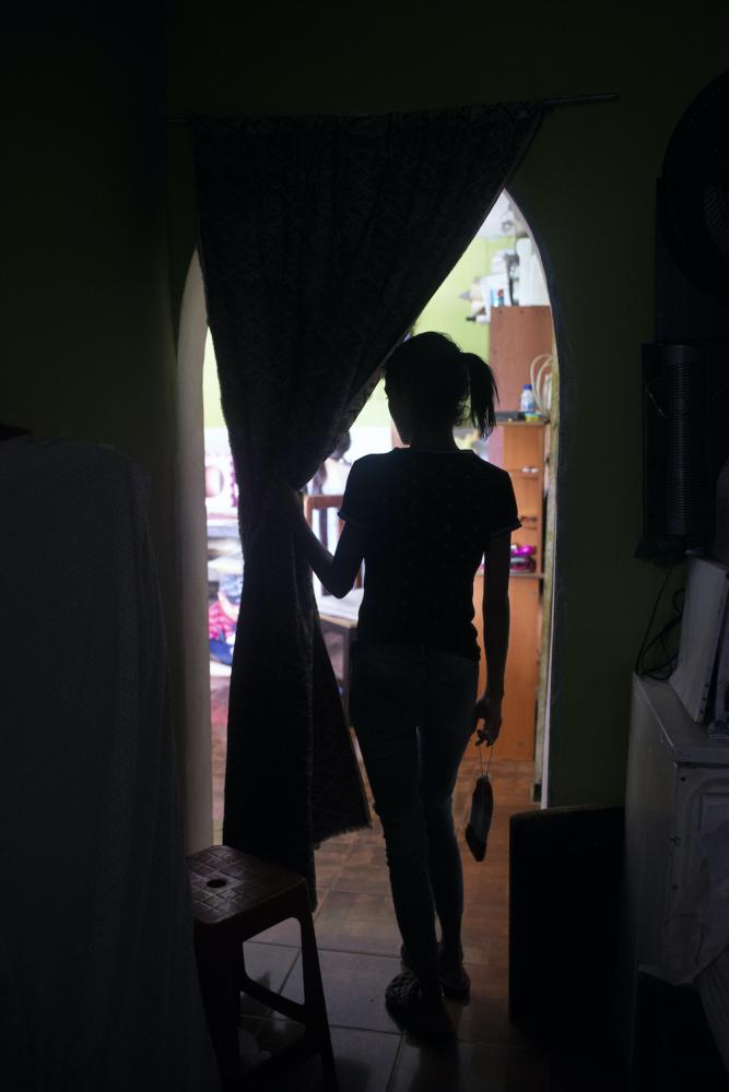 GUARENAS, VENEZUELA - JULY 12, 2020. Julieth walks through the hallway of the apartment to the living room. She is grateful for the support of her family, but constantly wonders in the future she can give to her son here in Venezuela. CREDIT: Lexi Parra