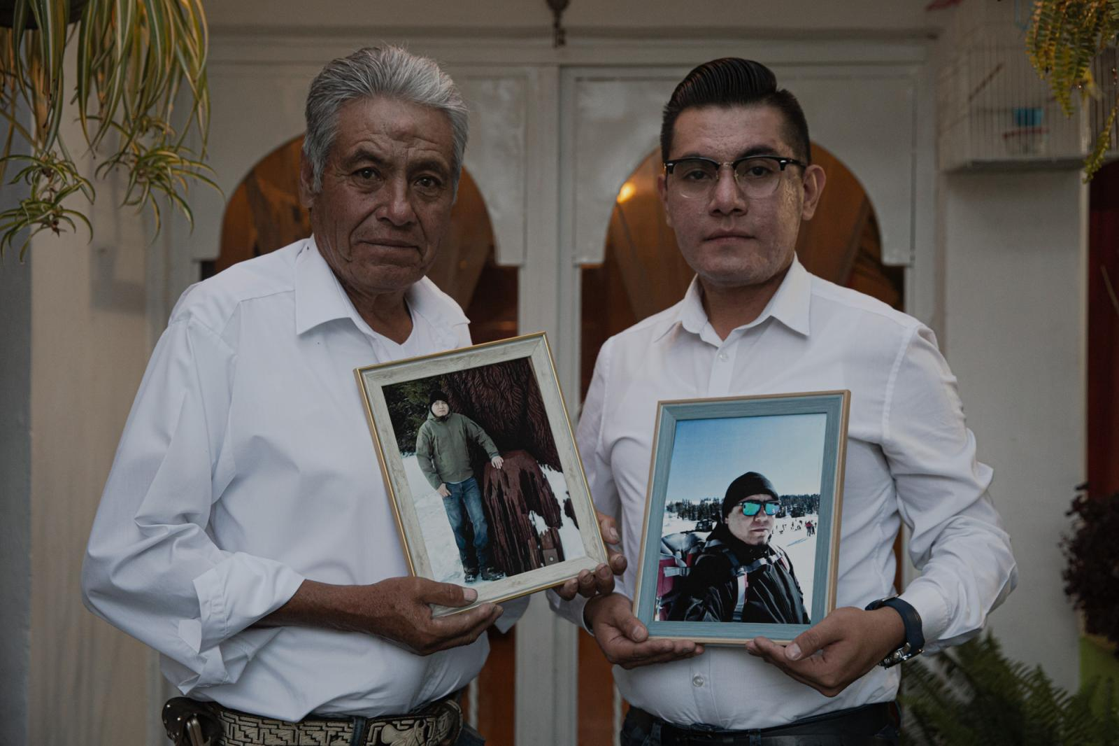 Pedro Martinez Hernandez and Javier Martinez Chichil, hold the photo of Juan Pedro Martinez Chichil, 36 the eldest brother of this family, who died of Covid-19 last April in Stockton, CA. For The Guardian.