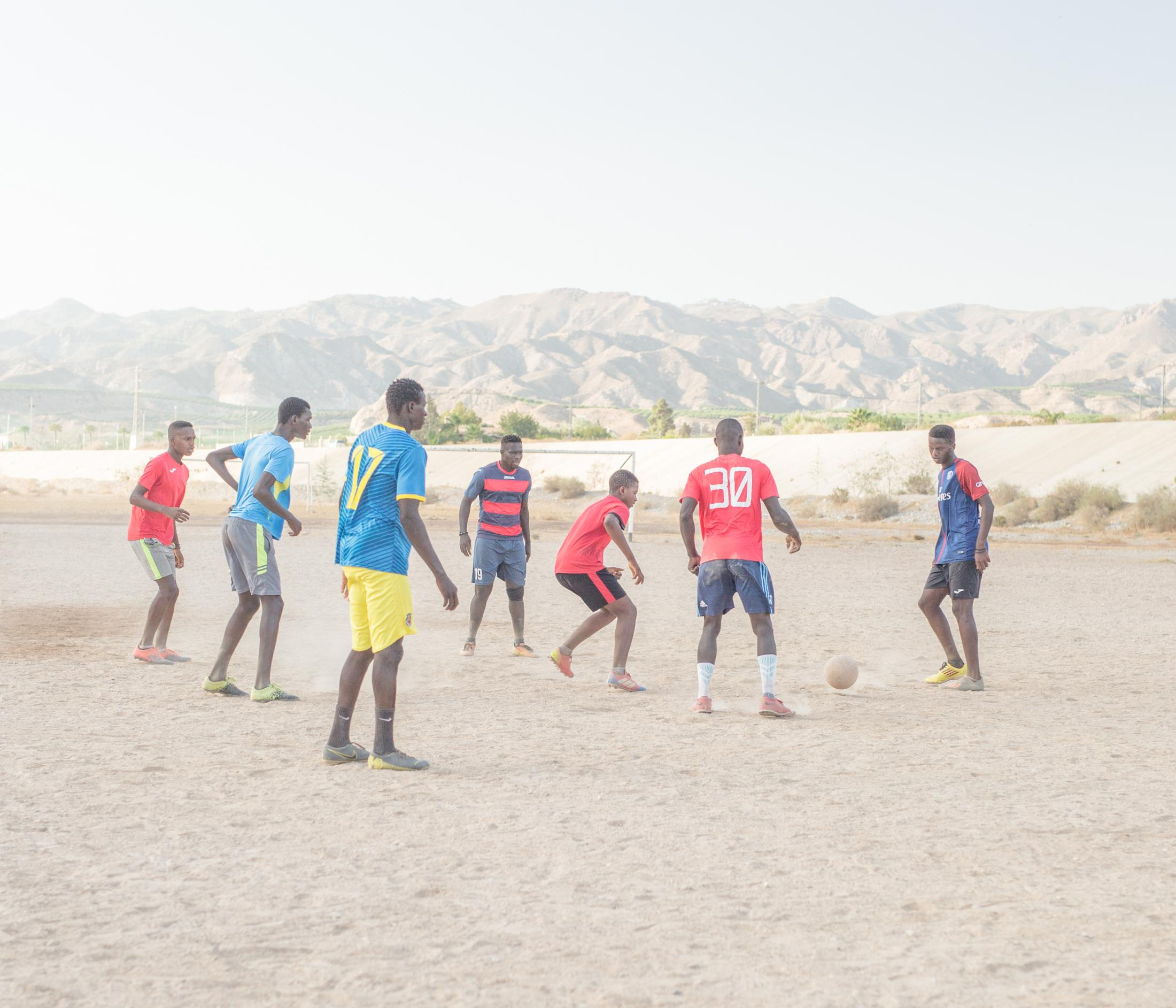 Instead of water flowing down, there is football. Some young people from Senegal enjoy a match every single day at 7pm (but Mondays), in the outskirts of Cuevas del Almanzora (Almeria), where is located the Almanzora, an almost completely dried-out river during its course due to droughts and agricultural industry practices. Several companies control the water coursing of this scarce land. Almeria. Cuevas del Almanzora, August 2020.