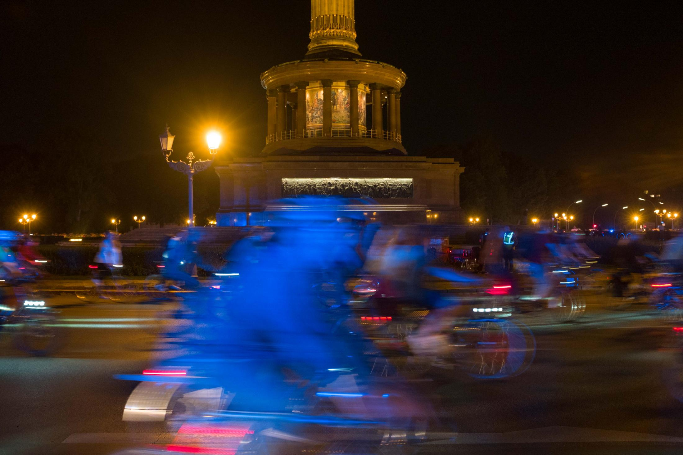 The blue light from police cars reflects off of participants of the monthly Critical Mass bike ride as it circles the Victoria column on Berlin's Großer Stern roundabout. Police presence is heavy all over the central parts of Berlin because of anti-government protests by a mixture of Corona deniers and neo-nazis. Berlin, August 28, 2020.