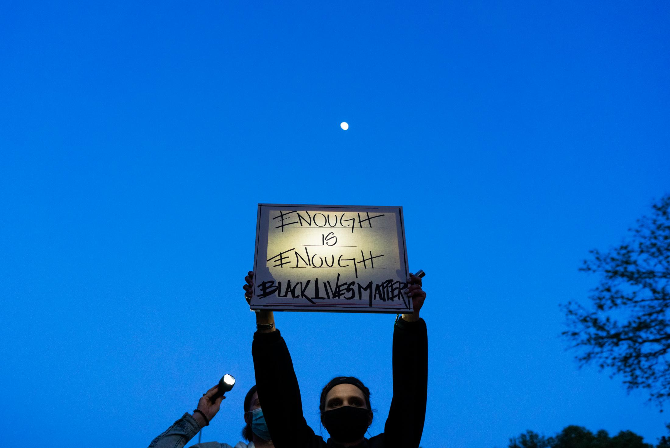 A vigil attendee holds a Black Lives Matter sign during a peaceful vigil for George Floyd on Monday, June 2020 in Astoria, New York.