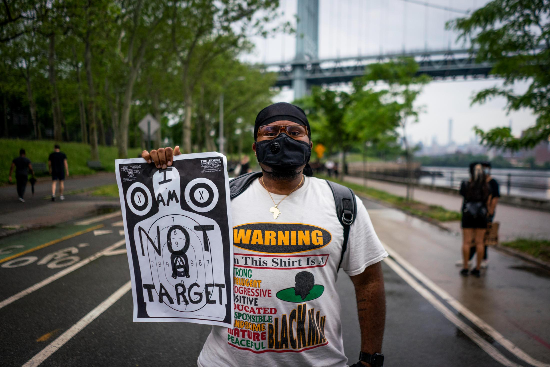 Matt M. holds up a shooting range target while attending a vigil for Breonna Taylor at Astoria Park in Queens.