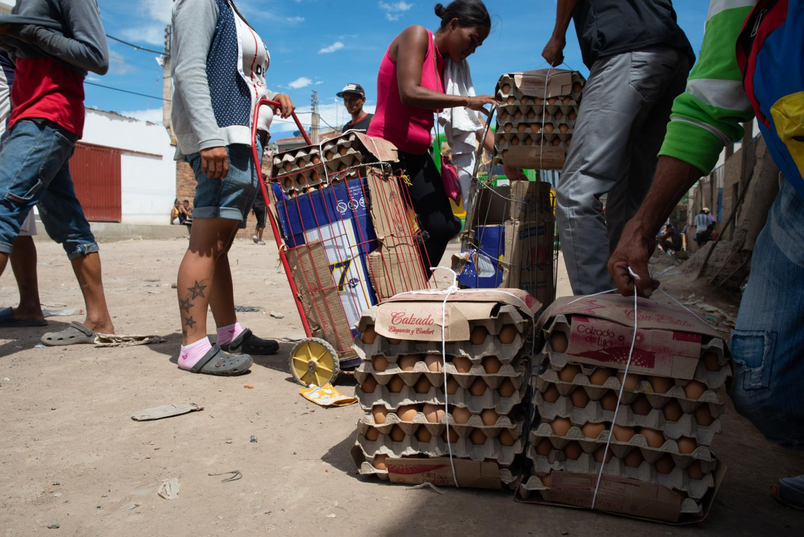 Zully and Nelly are charging their carts with eggs and other goods to carry over to Venezuela. The carriers, or Garrucheras, are paid an average of 5,000 - 10,000 COP (2-3 USD) per trip, depending on the weight. Nelly once earned 50,000 COP ($13 USD) for a heavy load. La Parada, Colombia - October 9, 2019.