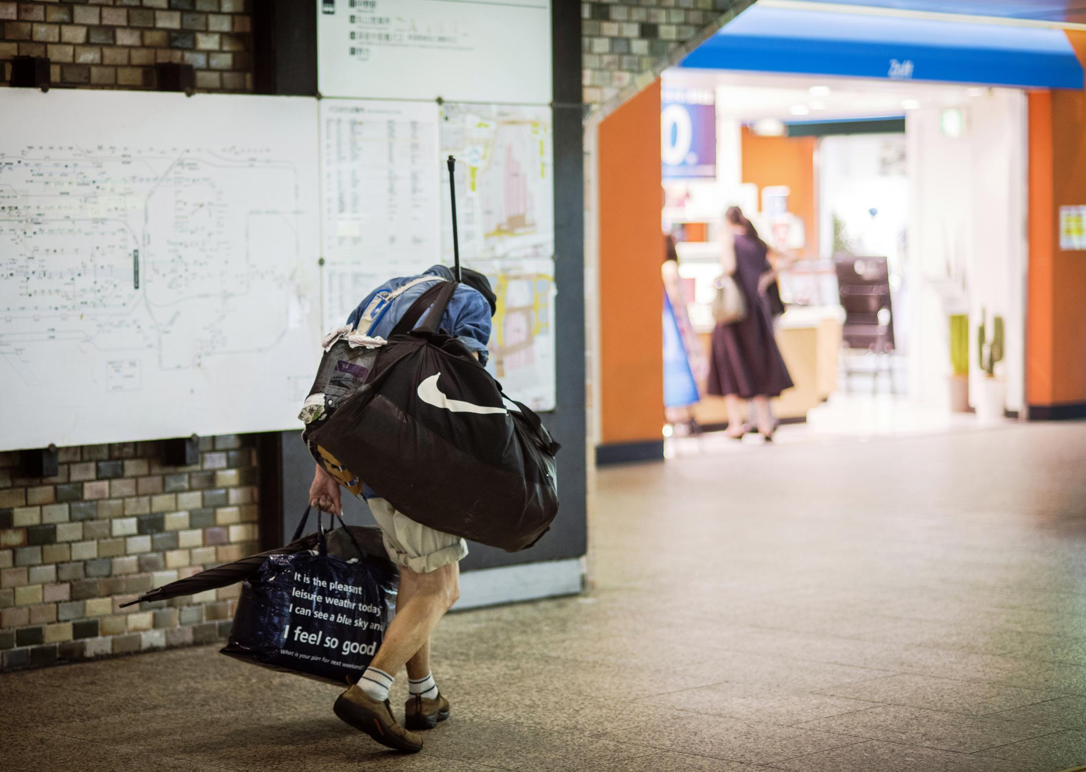 A homeless man wanders around  Shinjuku station, Tokyo, in the time of COVID-19.