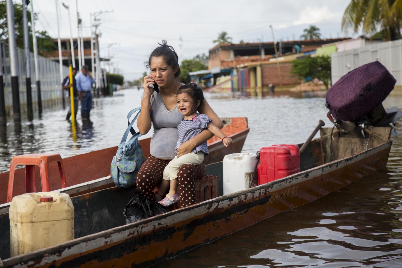 Una mujer intenta hablar por celular con su hija en brazos, mientras esperan que el conductor de la canoa inicie el camino, en Guasdualito, estado Apure, el 6 de julio de 2015.