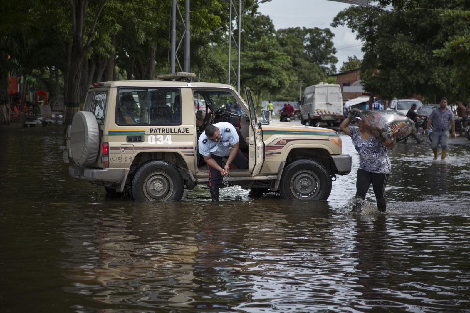 Un policía se lava las manos en el agua estancada producto de la inundación, mientras una mujer carga en sus hombros una bolsa de ropa seca, en Guasdualito, estado Apure, el 5 de julio de 2015.