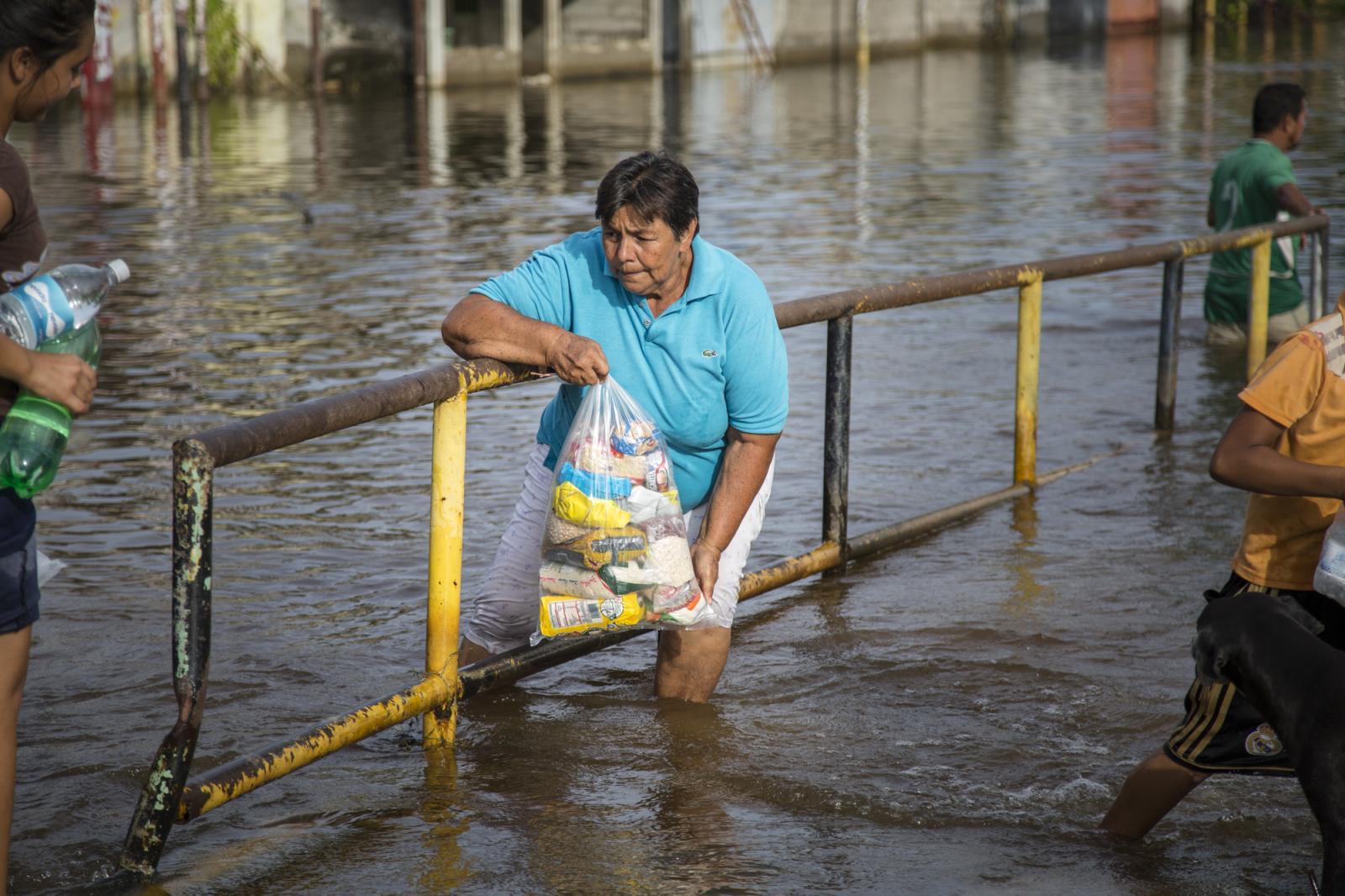 Una señora cruza una calle inundada cargada una bolsa de comida en Guasdualito, estado Apure, el 5 de julio de 2015.