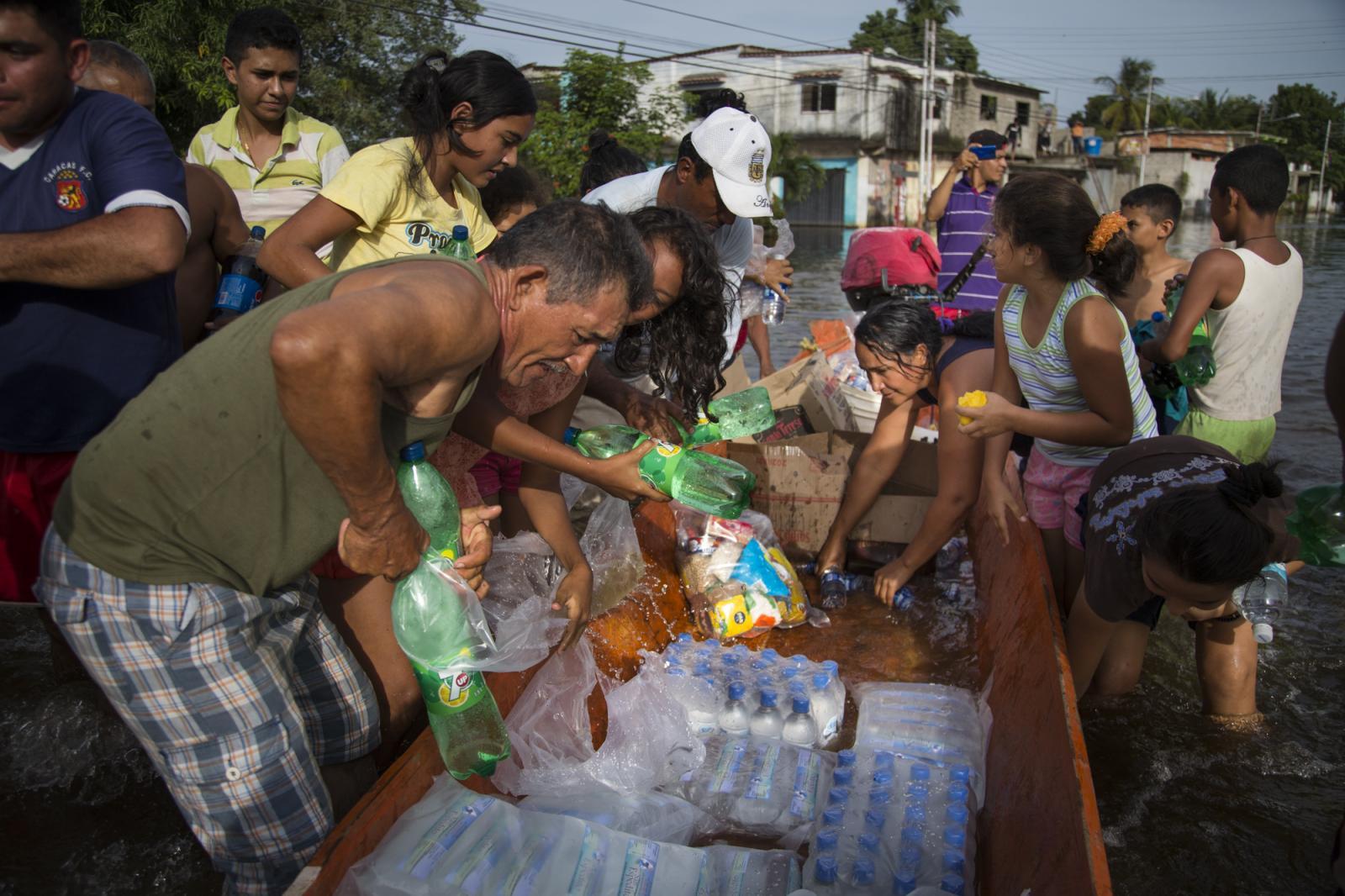 Habitantes de Guasdalito, afectados por la inundación, se llevan de una canoa agua y comida enviada por el gobierno el 5 de julio de 2015.