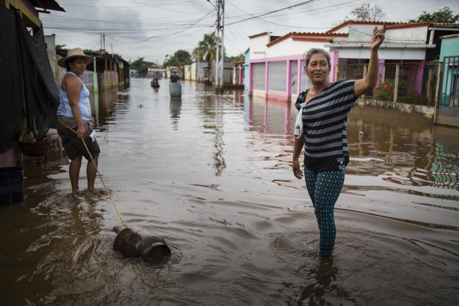 Una mujer arrastra por el agua una bombona de gas, mientras otra señala al río en Guasdualito, estado Apure, el 5 de julio de 2015.