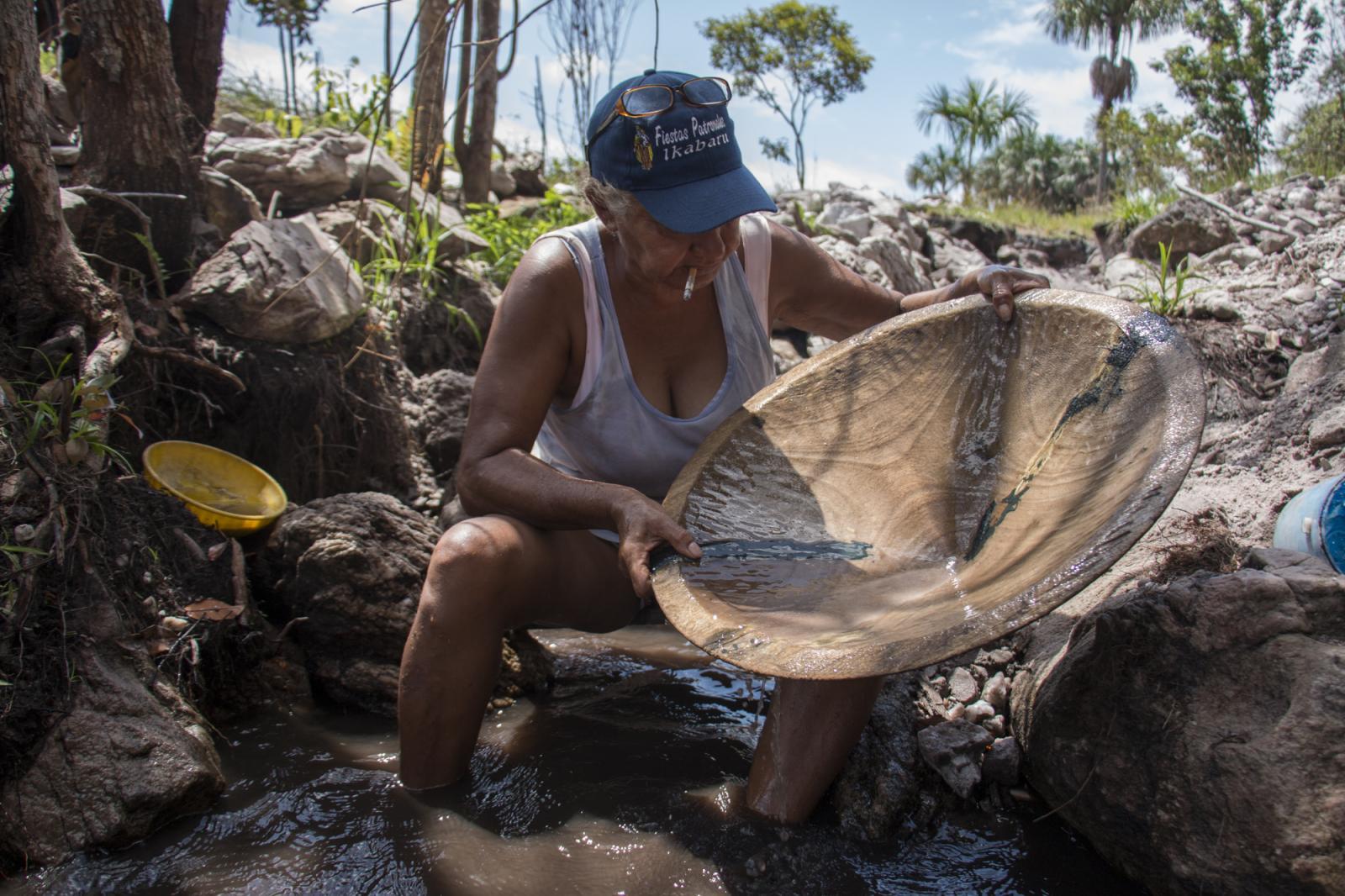 Luisa Girón, una minera de 62 años, busca oro con su batea en una veta en Ikabarú, estado Bolívar, el 4 de junio de 2016. Luisa estudió y vivió en Caracas por muchos años, pero regresó a su pueblo natal y se dedicó a ser palera, nombre que se le da las mujeres dedicadas a la minería artesanal. Tiene dos hijas, una en Tenerife, España, y la otra en El Callao, un pueblo a 195 kilómetros. Luisa es de una familia de 14 hermanos en la que todos son mineros.