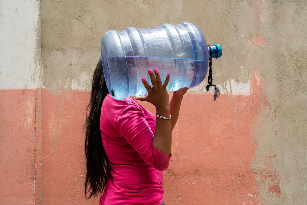 CARACAS, VENEZUELA - OCT 7, 2019 A woman in a commune in La Vega, a neighborhood in West Caracas, carries a bottle of water to her home. Communes are a people-powered and state-supported organization originally implemented by Chavez during his presidency.