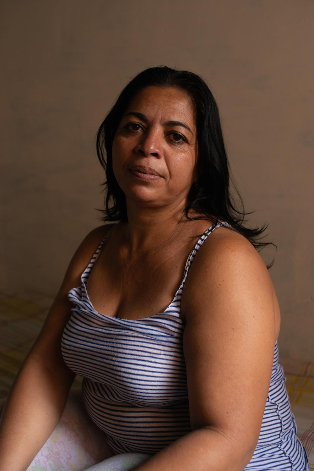 CARACAS, VENEZUELA - JUNE 2, 2019 Nancy poses for a portrait in her home in El Tamarindo, a barrio of Caracas. Her neighborhood 'territory' has been fought over by rival gangs for years. CREDIT: Lexi Parra