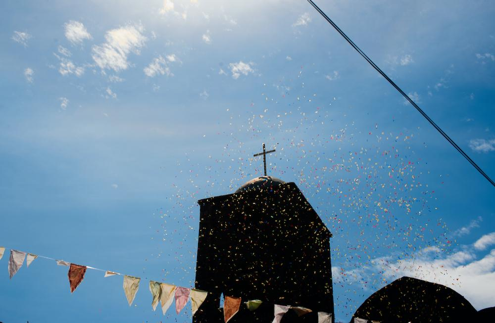 NAIGUATA, VENEZUELA - JUNE 24, 2019 Confetti is thrown into the air in front of the local church as the town of Naiguata celebrates San Juan, a Catholic tradition paired with drumming and a massive parade. Credit: Lexi Parra