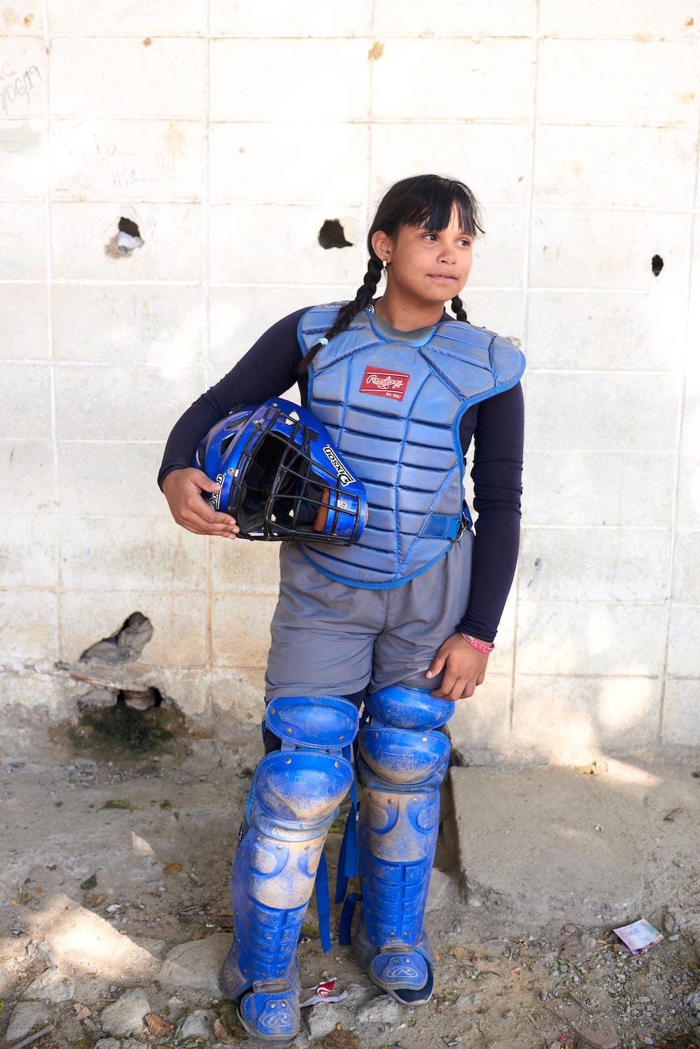 CARACAS, VENEZUELA - FEB 10, 2020 Maria, a 14 year old baseball player, poses for a portrait at her academy. The local academy works to train young talent as parents hope that their child will be picked up by a US team, providing financial security as the crisis continues. Credit: Lexi Parra