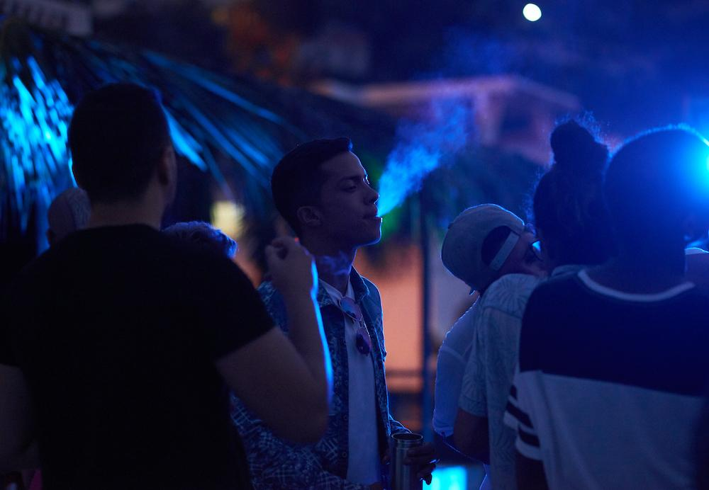 LA GUAIRA, VENEZUELA - FEB 24, 2020 A party-goer smokes a cigarette in a group of people dancing. The party was for the elite of Caracas' LGBTQ community, held at a private residence with a high entry fee charged in US dollars. Credit: Lexi Parra