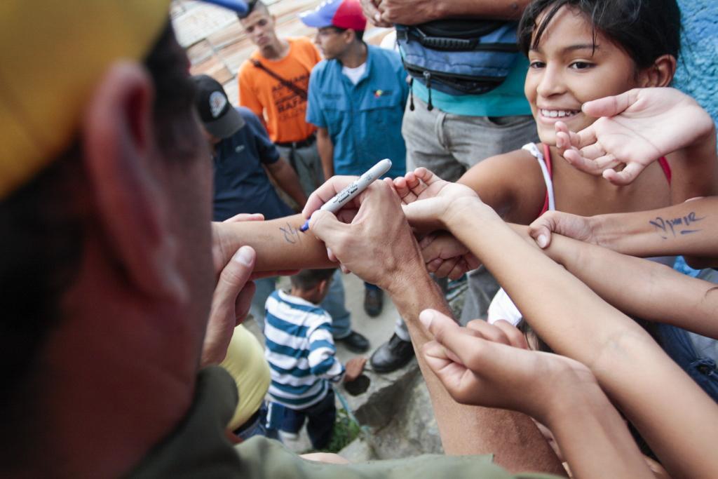 Henrique Capriles Radonski, Gobernador del Estado Miranda (Venezuela) firma autógrafos a niños del sector Quebrada El Oro en Guarenas luego de una reunión con vecinos del sector. Guarenas, Venezuela. 28/10/2015.