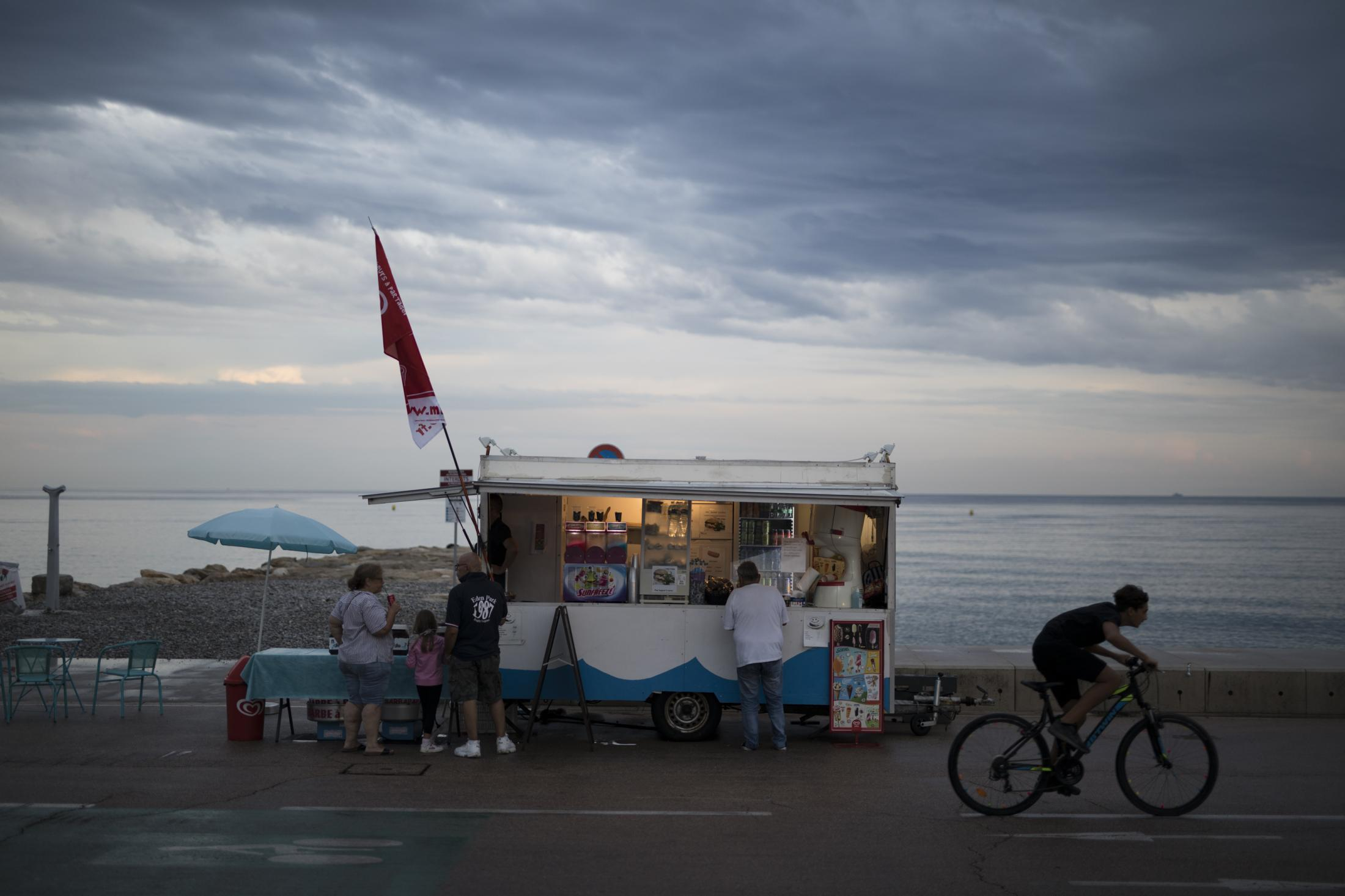 People enjoy refreshments along the beach promenade in Cagnes-sur-Mer the day of the first stage of the 107th Tour de France cycling race, Friday, Aug 29, 2020. (AP Photo/Daniel Cole)