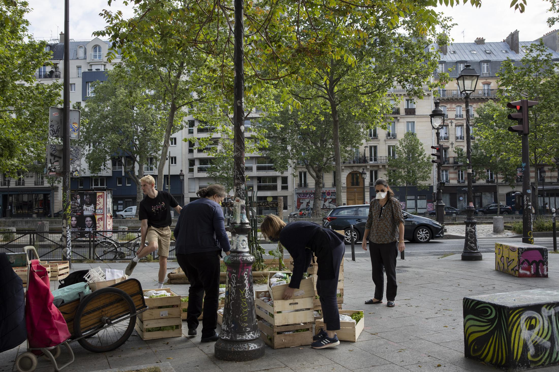 The baskets of products unloaded on the Place du Quai Valmy in Paris before the opening of distribution by La Ruche Qui Dit Oui. More than ten volunteers come to work in the sale and distribution of baskets during quarantine. Hundreds of people pass by during the distribution, some discover the services and the interest by the networks like that of the Hive is in full rise in France. Paris, France, April 2020